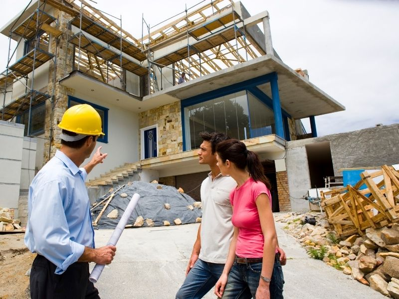 a man and woman standing anf talking to a contractor in front of a home under construction