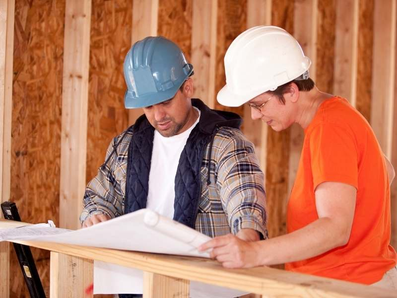 men in hardhats iooking over blueprints for a home