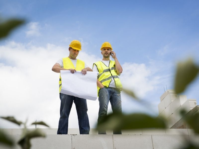 two men standing on a step in contractor gear, one is rolling up a schematic